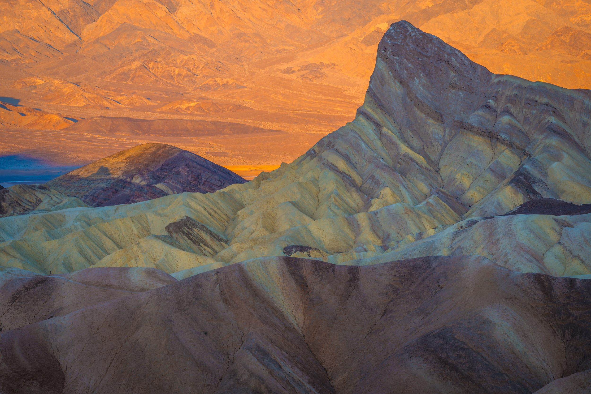 Warm morning light bathes the mountains in the background at Zabriskie Point in Death Valley