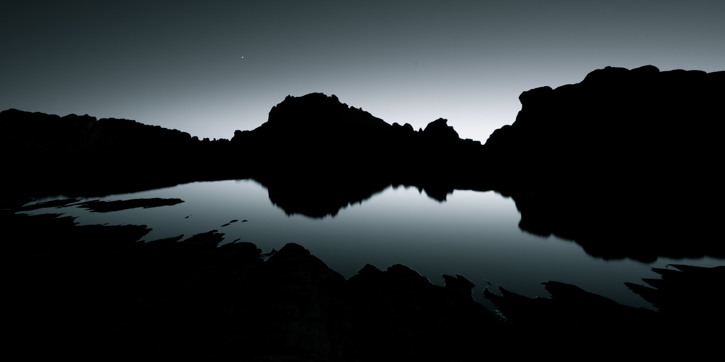 Rock formations and water pools at twilight in White Pocket, Arizona