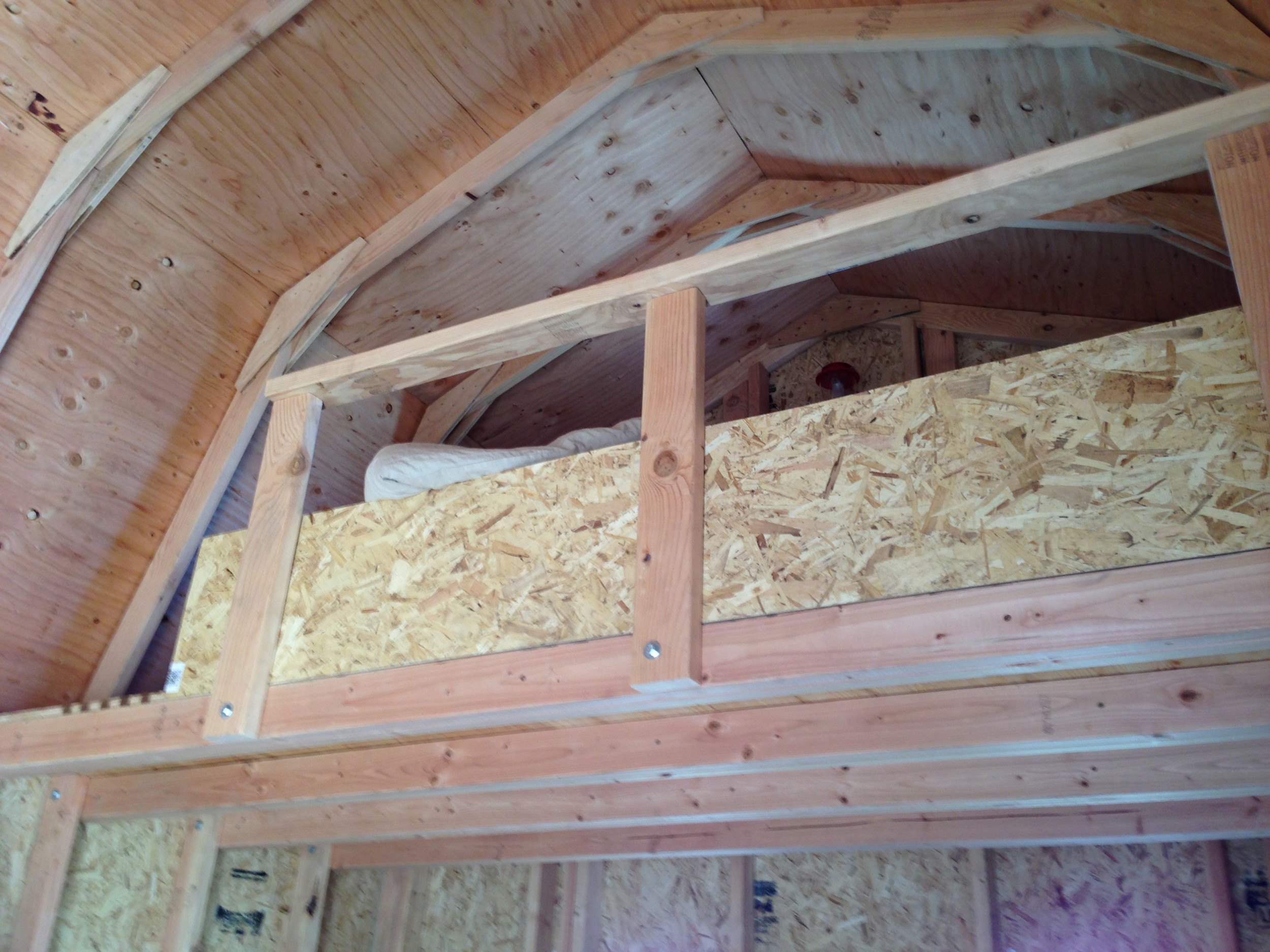 We fastened the railing to the joists with the same hardware used to attachthe joists to the studs, making the railing extremely sturdy. The extra piece of siding was a temporary wall to prevent my phone and eyeglasses from getting knocked off unintentionally.