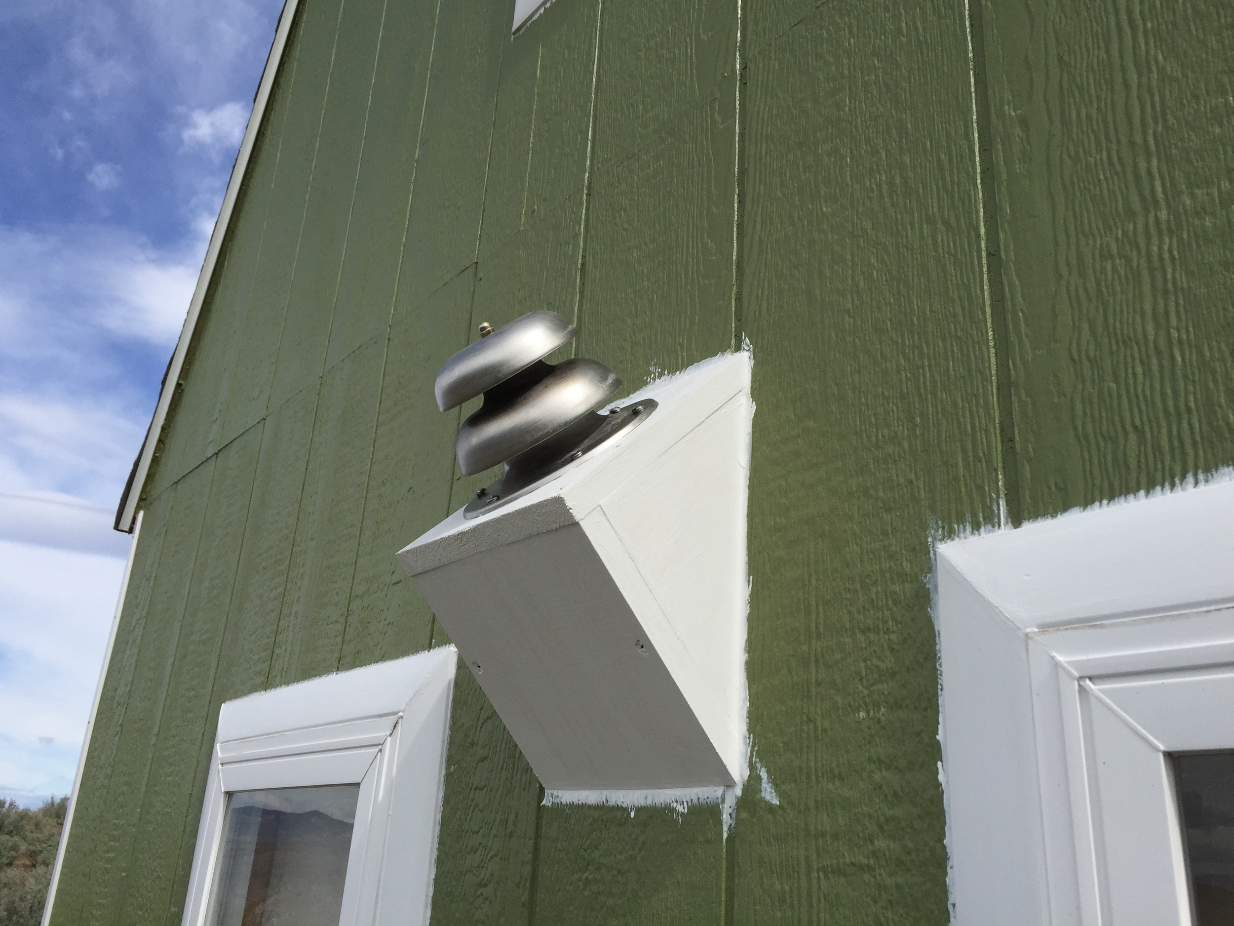 The back side of the cabin now houses the fireplace flue—a dual intake/exhaust pipe with a bell cap.