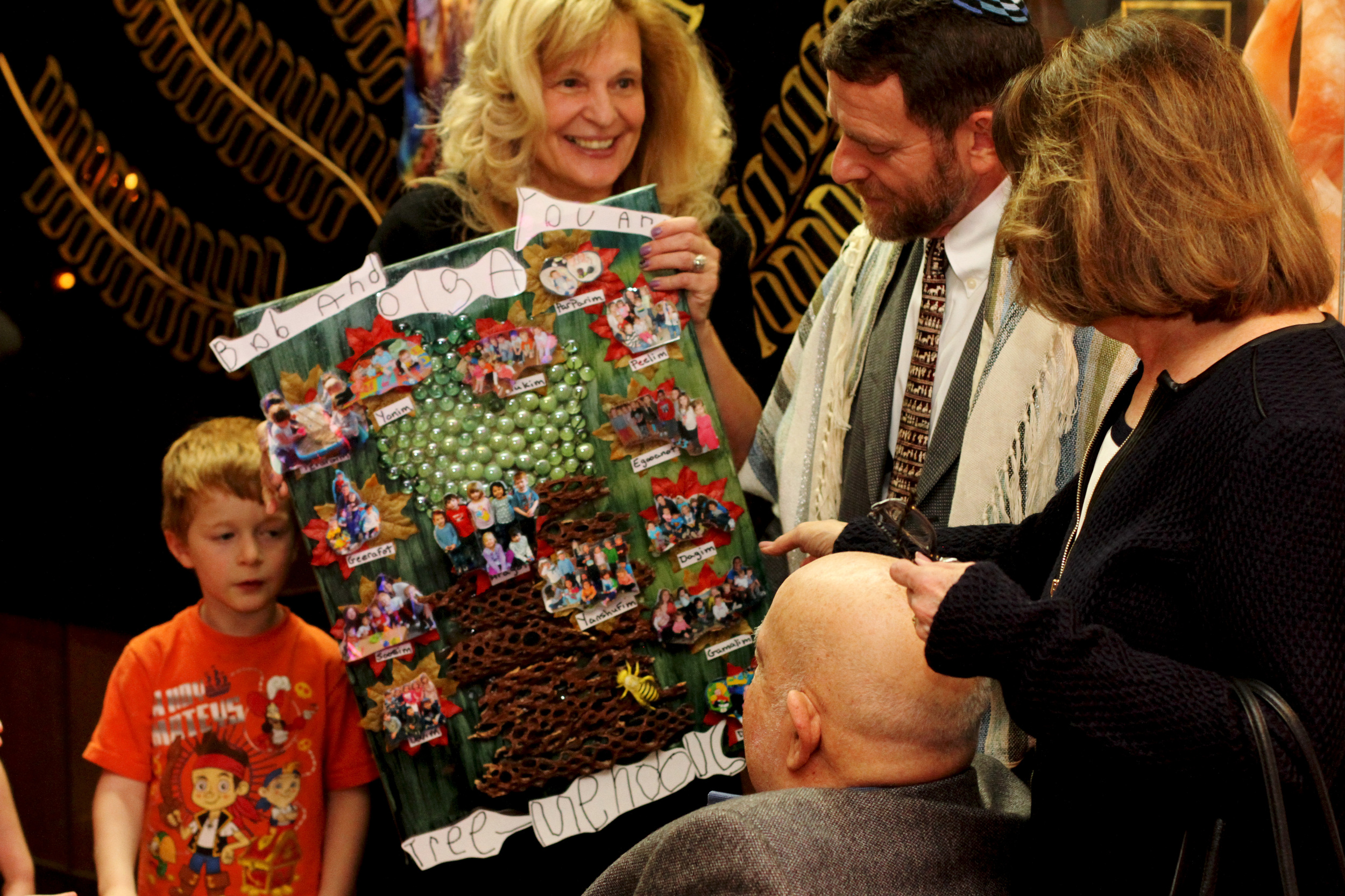 A child and the day care director present the artwork