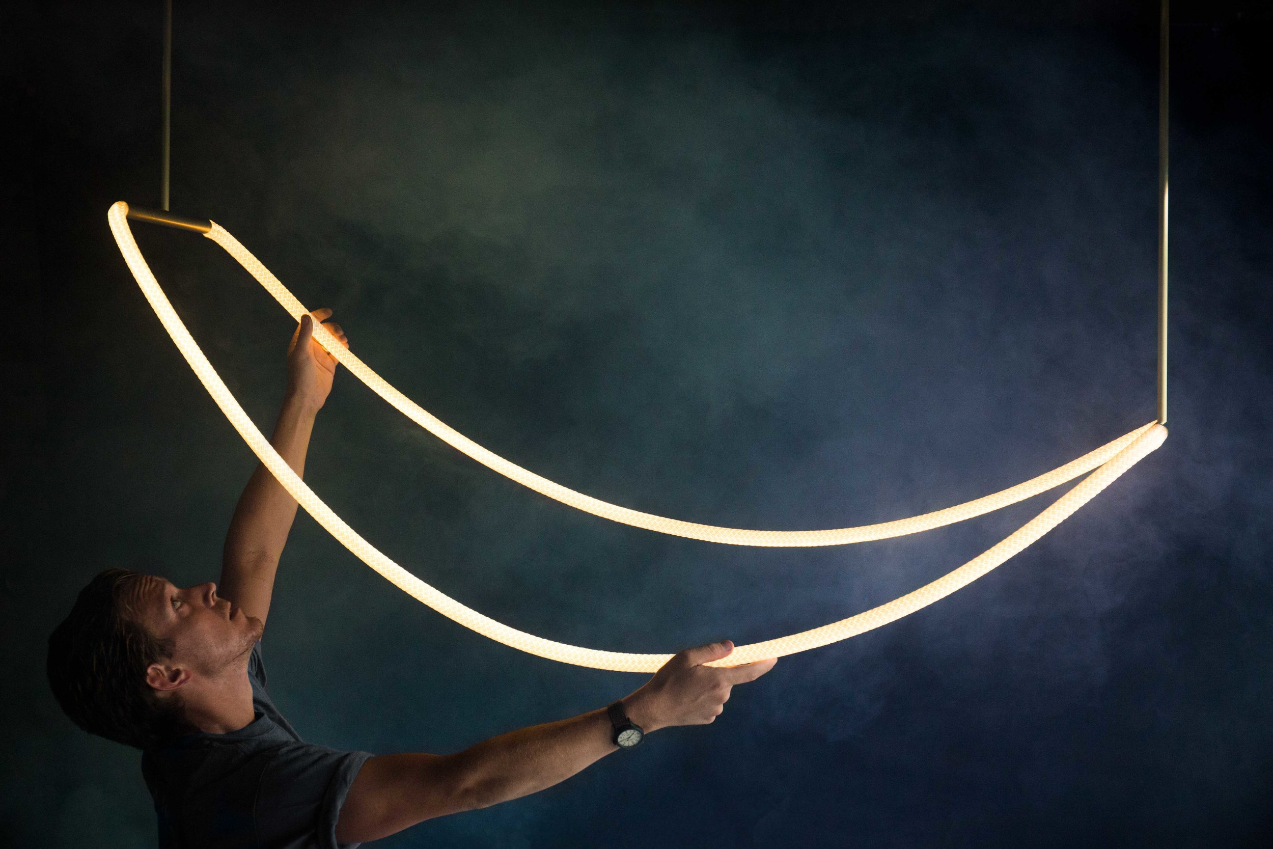 Constrained yet organic, the Aura Chandelier is a statement piece designed to float effortlessly in any space, providing a warm ambient glow.    Pictured with brass hardware.