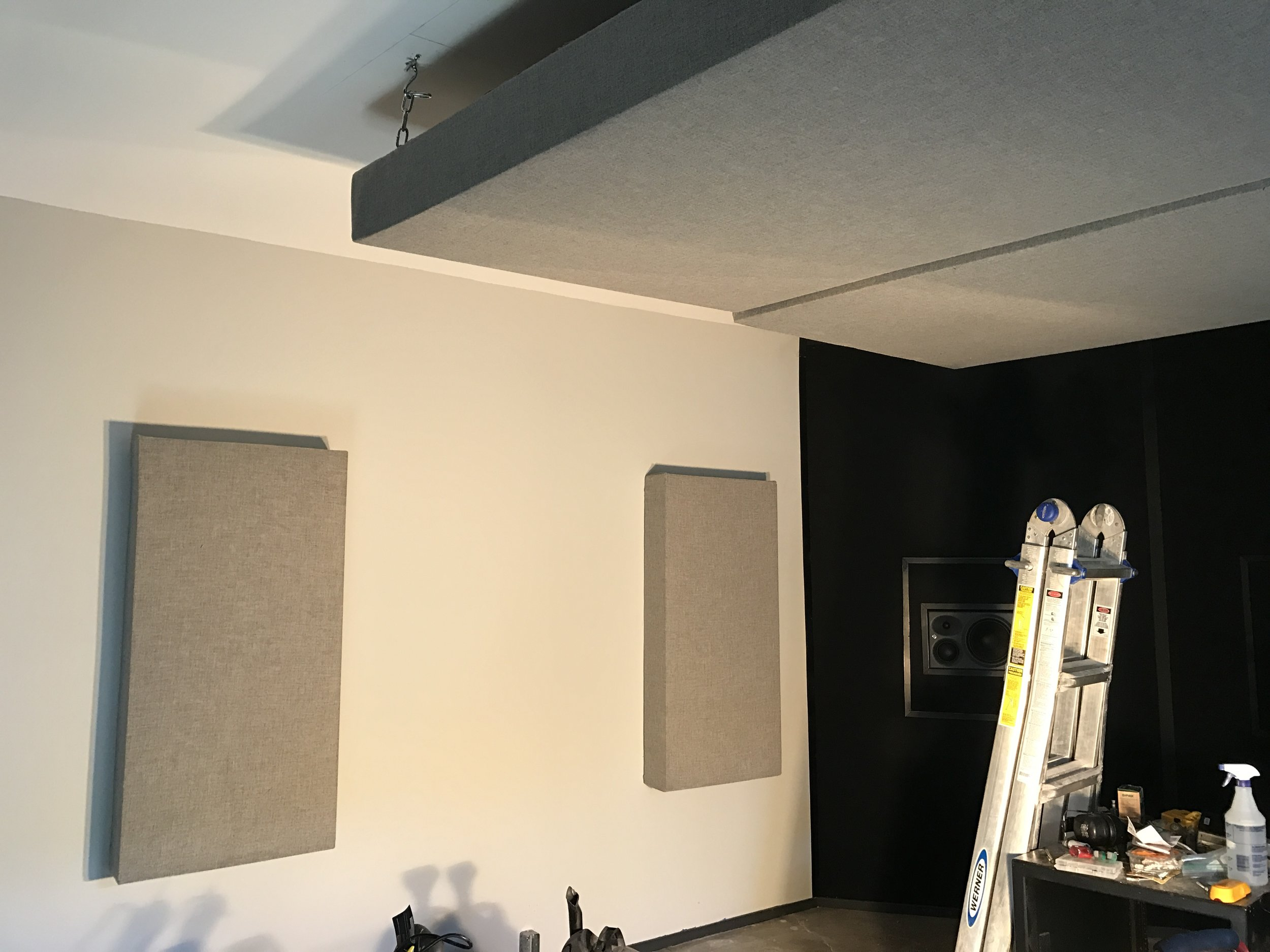 This is a shot of our new home studio which is currently under construction.  You can see two of the 2'x4' acoustic panels hung on the wall and two 4'x4' clouds hung from the ceiling. Please excuse the mess and the intense shadows in this photo.  We are about to embark on wiring our own electrical outlets today, so I used a work lamp to light this picture.