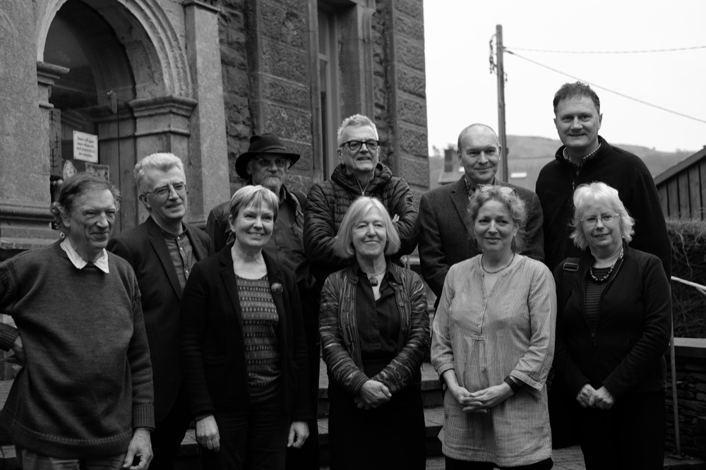 L-R at front: Charles Mapleston: Malachite Films; Diane Bailey: Penrallt Gallery Bookshop (Event organiser); Libby Horner: Malachite Films; Geraldine Alexander: Assistant to Fay Godwin; Marian Delyth: Photographer L-R at rear: Geoff Young: Penrallt Gallery Bookshop (Event organiser); Pete Davis: Photographer; Paul Hill: Photographer; Mike Parker: writer & broadcaster; Peter Cattrell: Photographer and Printer for Fay Godwin.