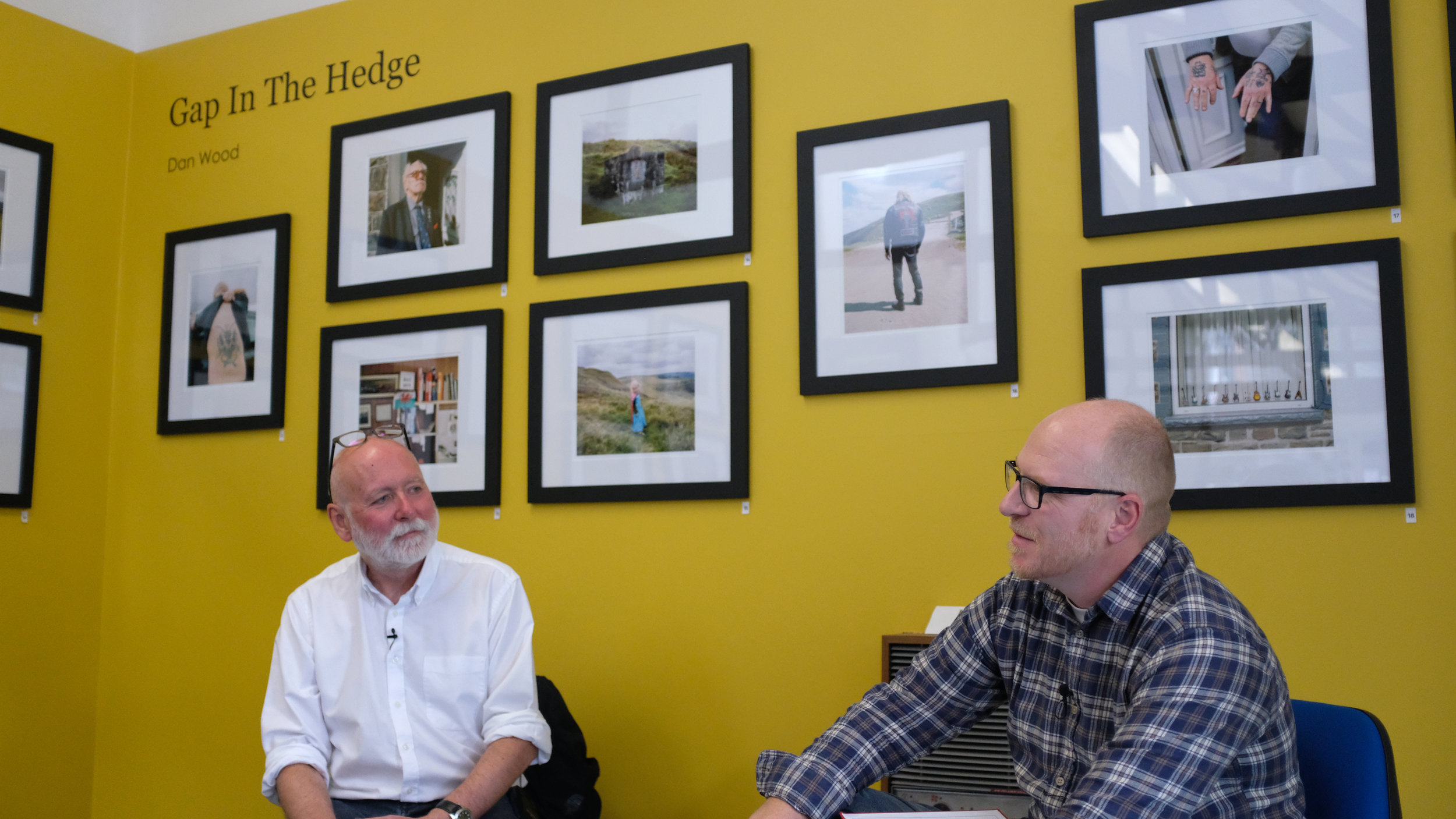Paul Cabuts and Dan Wood in conversation - with a selection of work from 'Gap in the Hedge' on the walls around them.