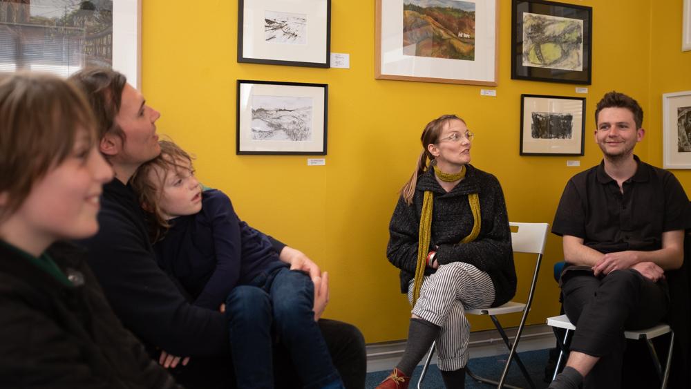 Anna Jones describing some of her work as family members look on.