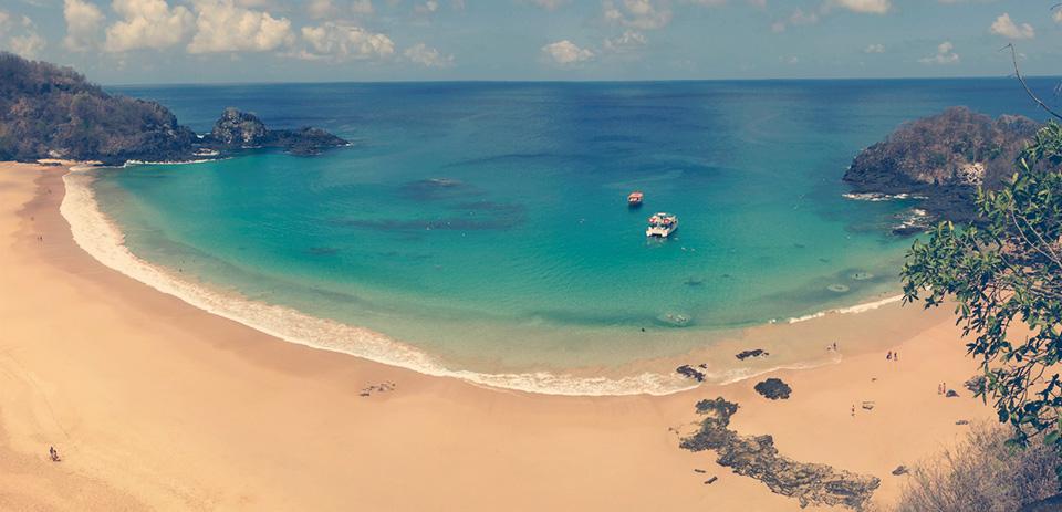 Mirante para a Praia do Sancho, eleita a mais bonita do mundo. As manchas escuras perto das ondas são sardinhas -elas formam um círculo ao redor dos banhistas.