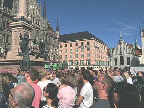 Multidão de turistas se reúne para assistir adança do relógio no alto da torre.