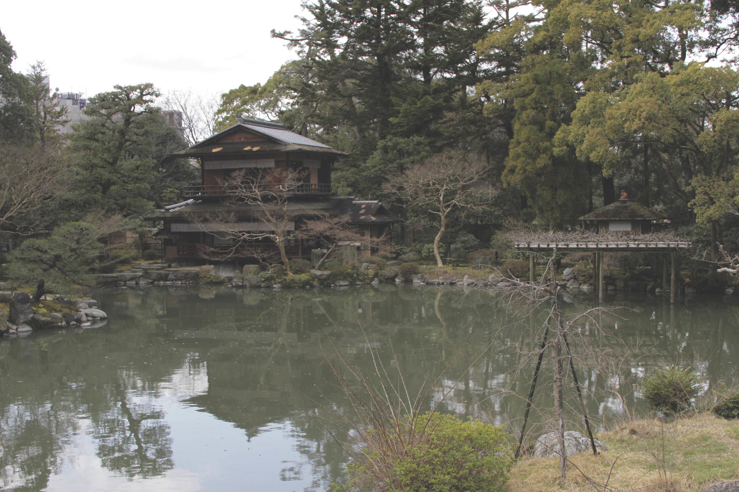 Uma casa de madeira a beira do lago que fica em uma das extremidades do jardim do palácio imperial.
