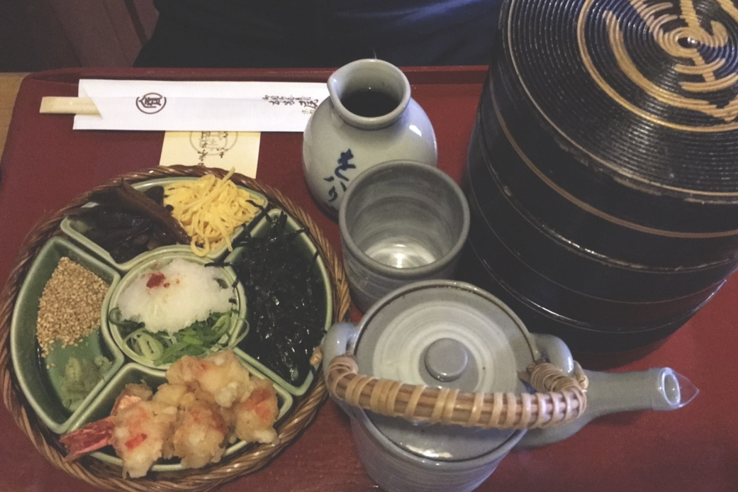 Prato de lamen do Honke Owariya. Do lado esquerdo há os ingredientes para se misturar junto com o molho e com as camadas de porções lamen que estão no recipiente do lado direito.