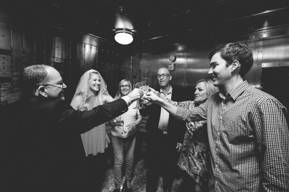 Couple celebrates with family after just getting engaged inside the 21C Hotel vault in downtown Durham.