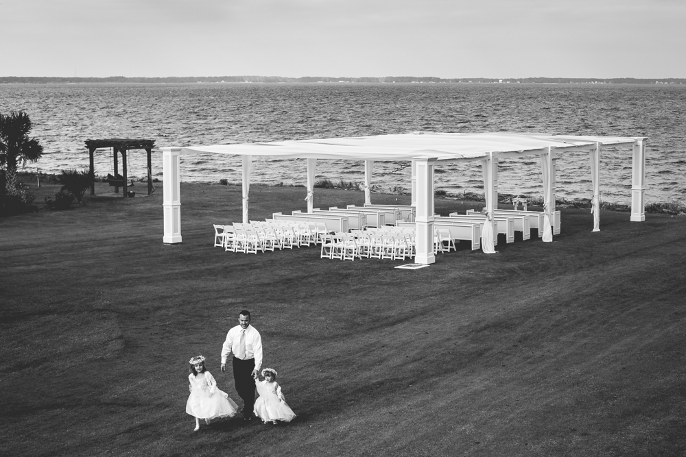 Two flower girls walking with their dad, right before the wedding at the beautiful Neuse Breeze Wedding Venue in Havelock, North Carolina.