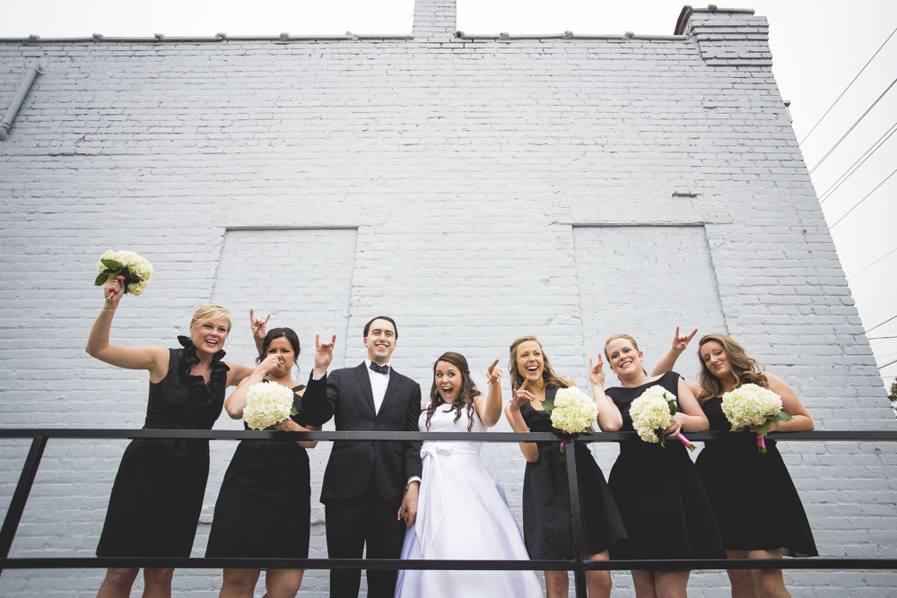 Bridal party having fun holding up the NC State Wolfpack sign for a photo.