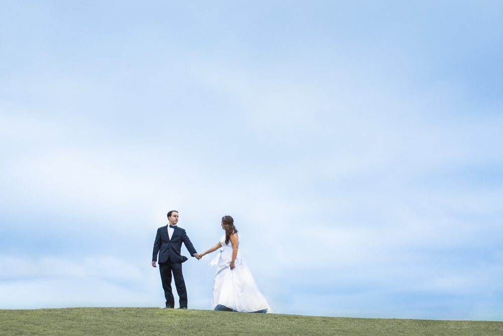 Rachel & Eric stroll across the greens of the NC State University Club Golf Course after their wedding.