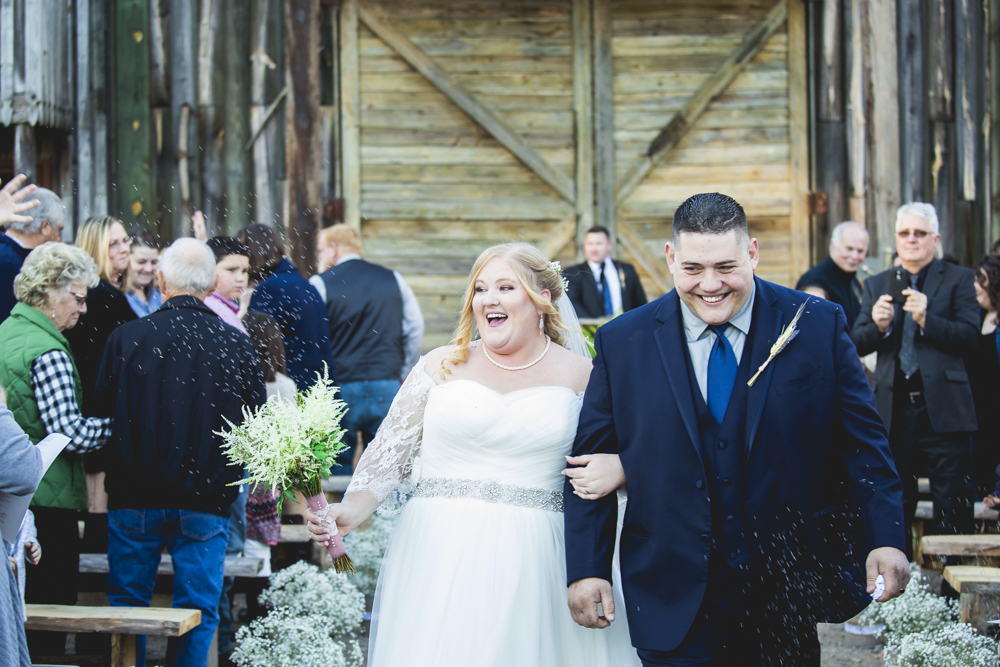 """Tara & Matt get lavender tossed at them as they exit their wedding ceremony after they said """"I do"""" at Circle M City in Sanford, North Carolina."""