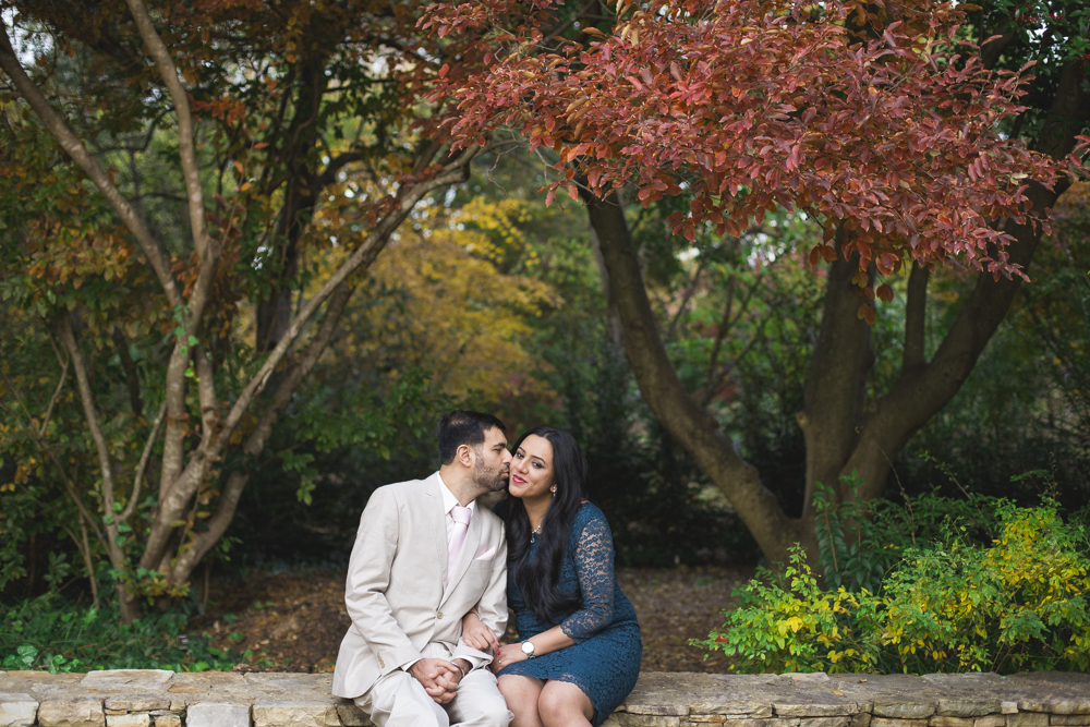 Engaged couple poses in front of the beautiful fall colors displayed at Raleigh's Raulston Arboretum.