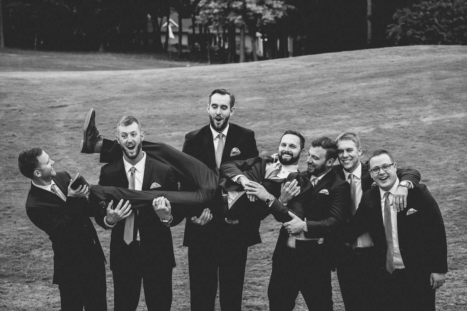 Groomsmen take a hilarious group photo during a wedding at Macgregor Downs Country Club.