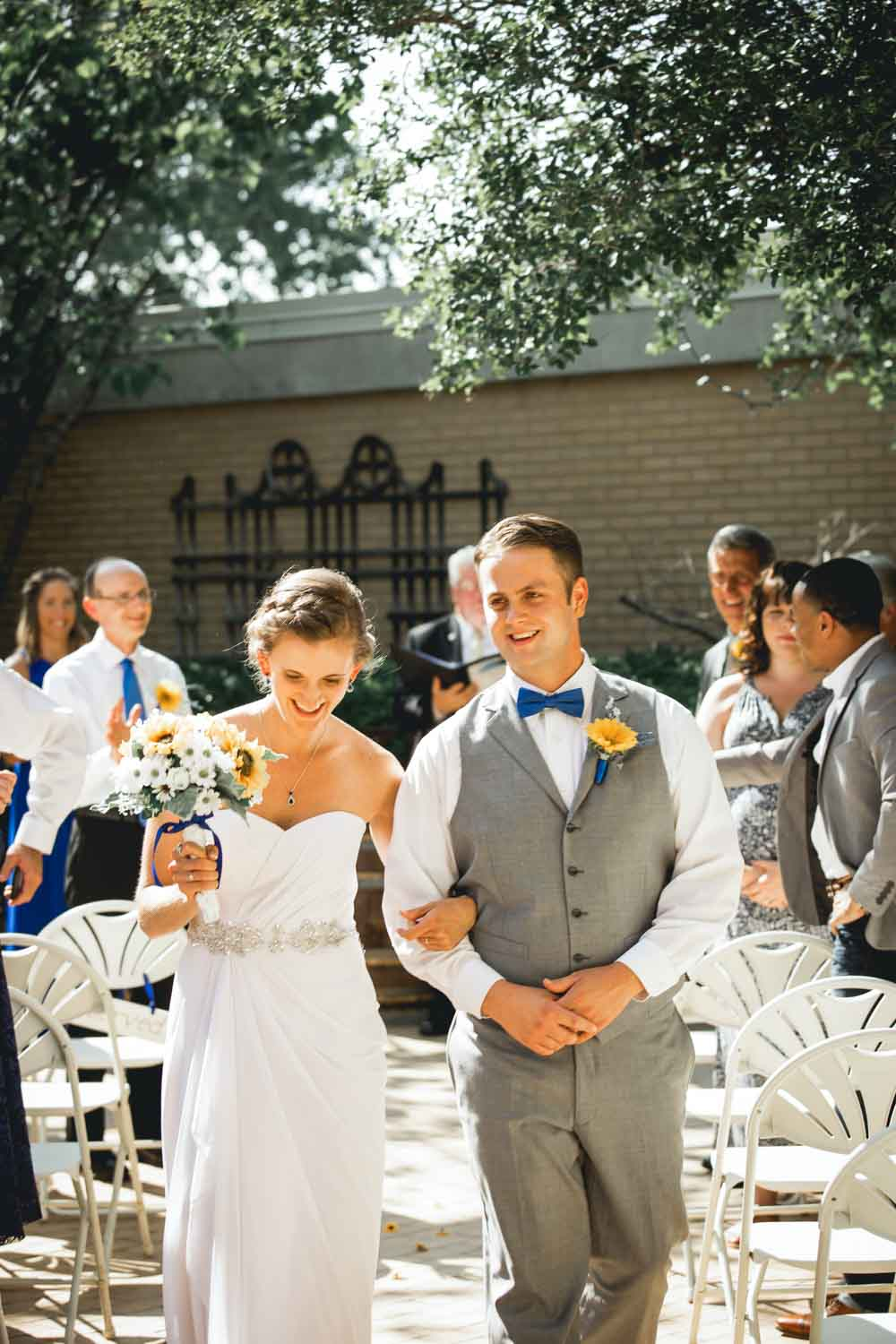 Megan & Josiah smile in celebration after getting married at Raleigh's NC State University Club wedding venue.
