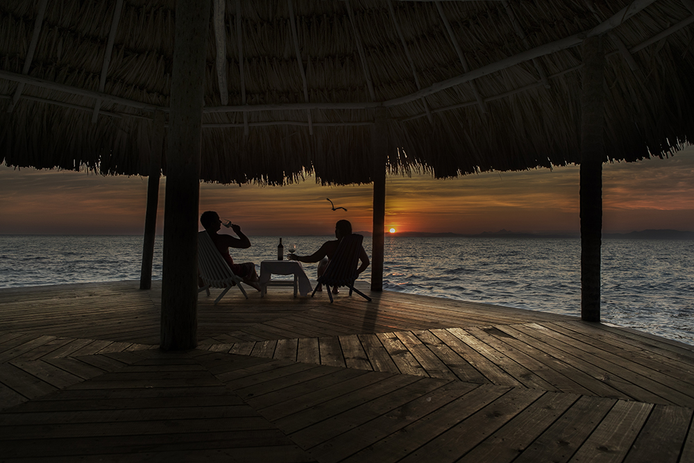 thatch caye wine at sunset on serenity point.jpg