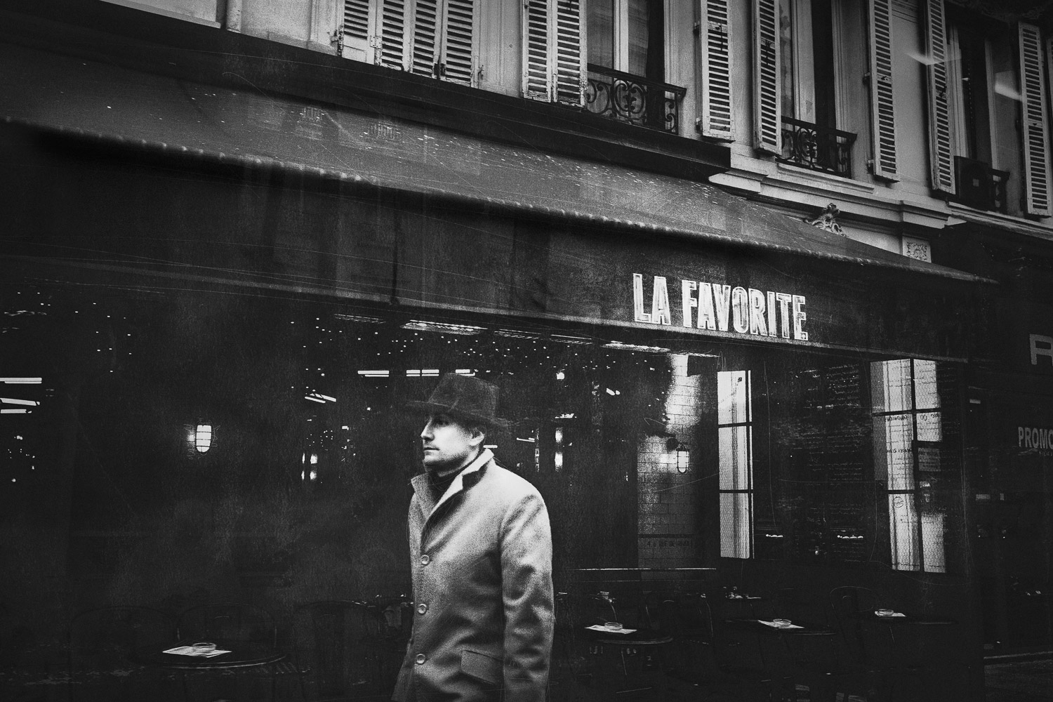 A man passes by cafe La Favorite, Paris, France