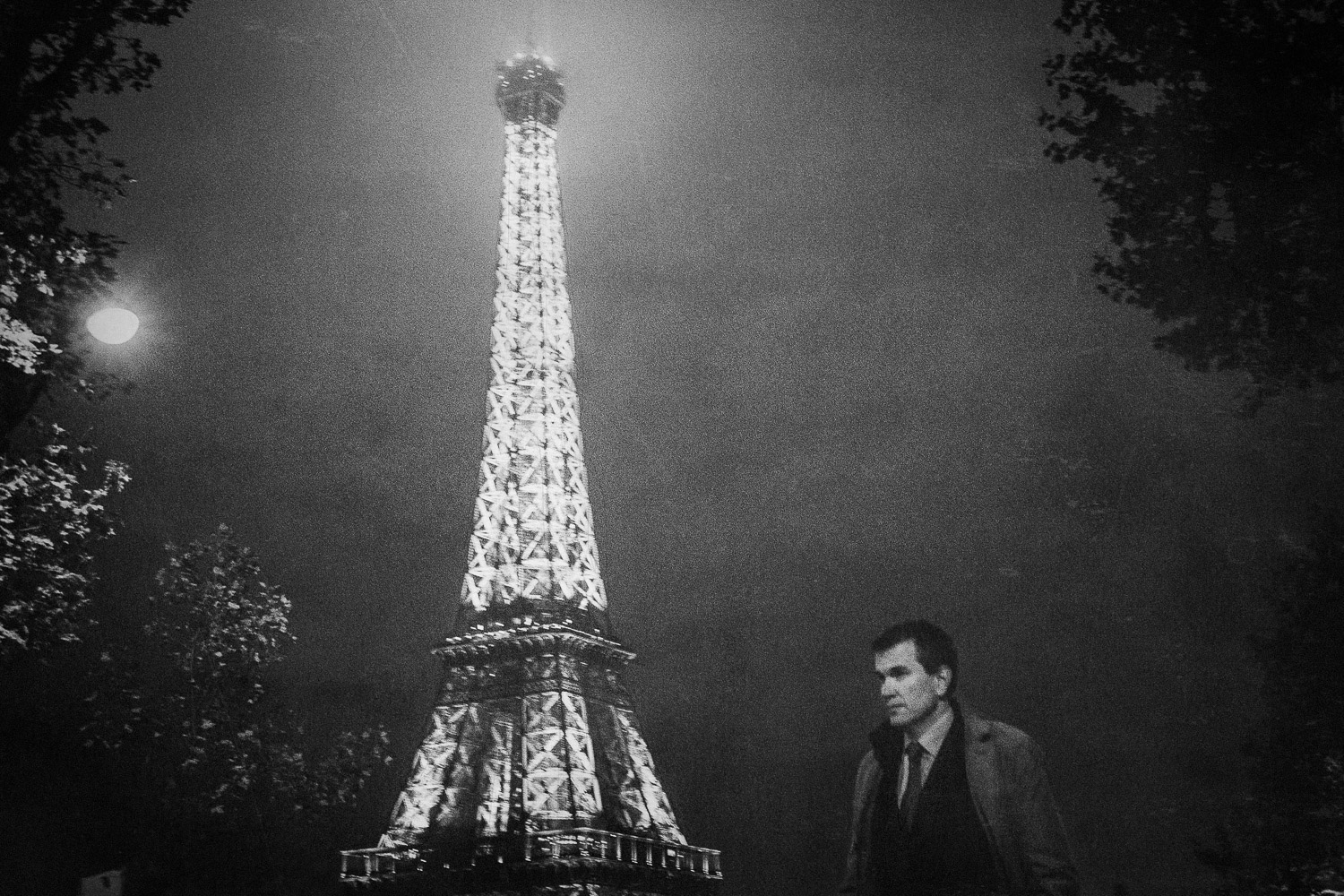A man passes the illuminated Eiffel Tower at night, Paris, France