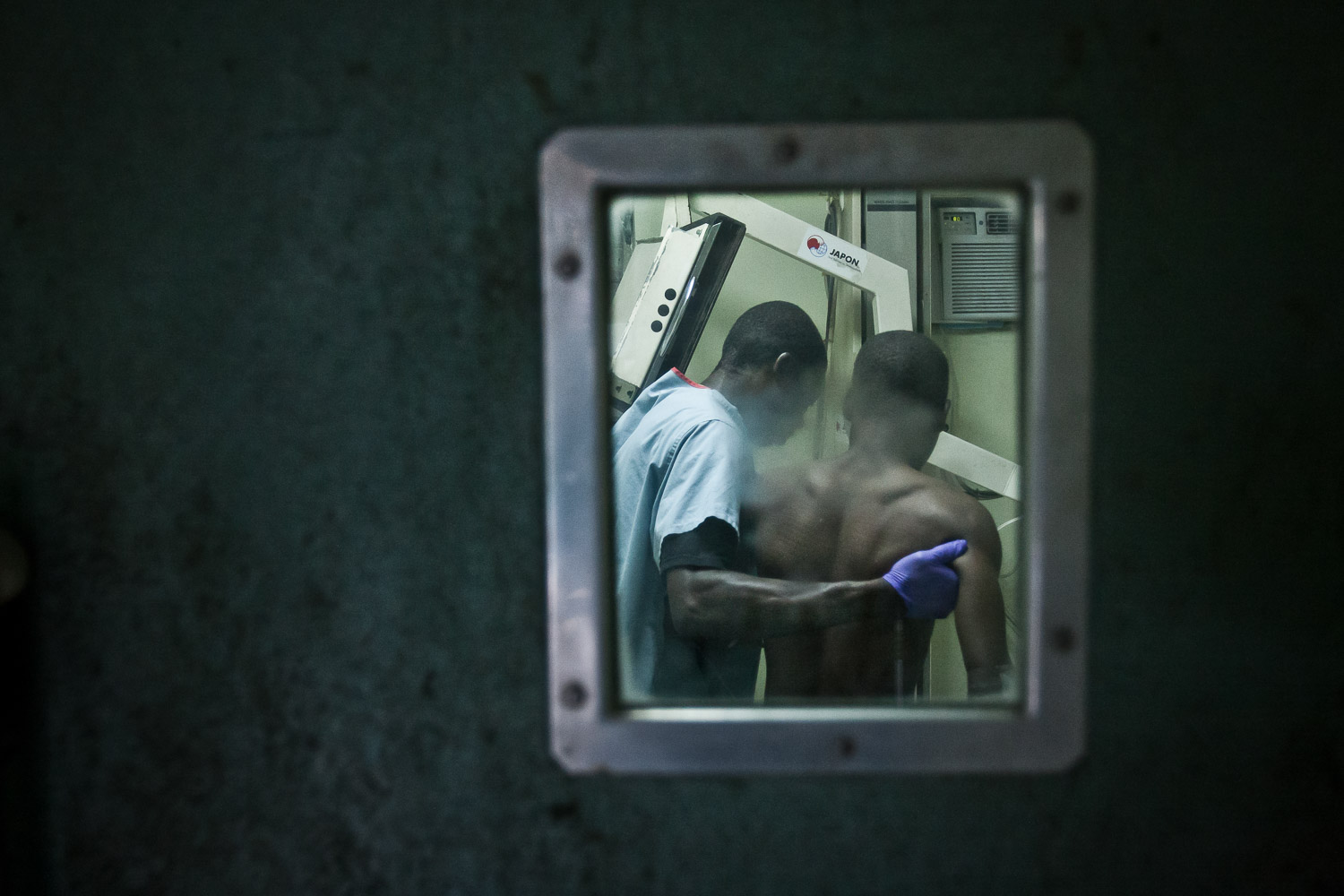 Port-au-Prince. A man with chest injuries is being supported to stand for an x-ray examination of his lungs.