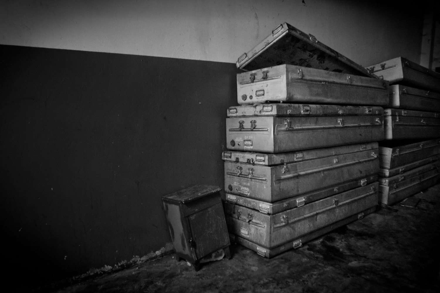 Empty metal coffins piled up in a corner of a hospital morgue outside the cold and crowded storing rooms. A deep humming from the air-condition echoes on the thick walls, breaking the deafening silence of the building.