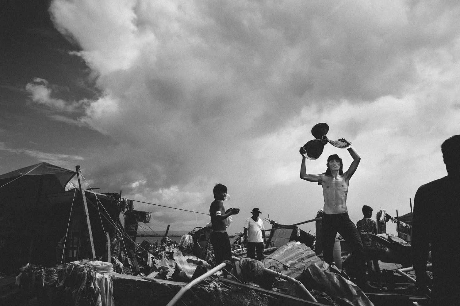 Tacloban City. A team of young men carry out the remains of a boat, piece by piece. The propeller is raised as the last and triumphant piece, before the team rush off on an open pickup truck.