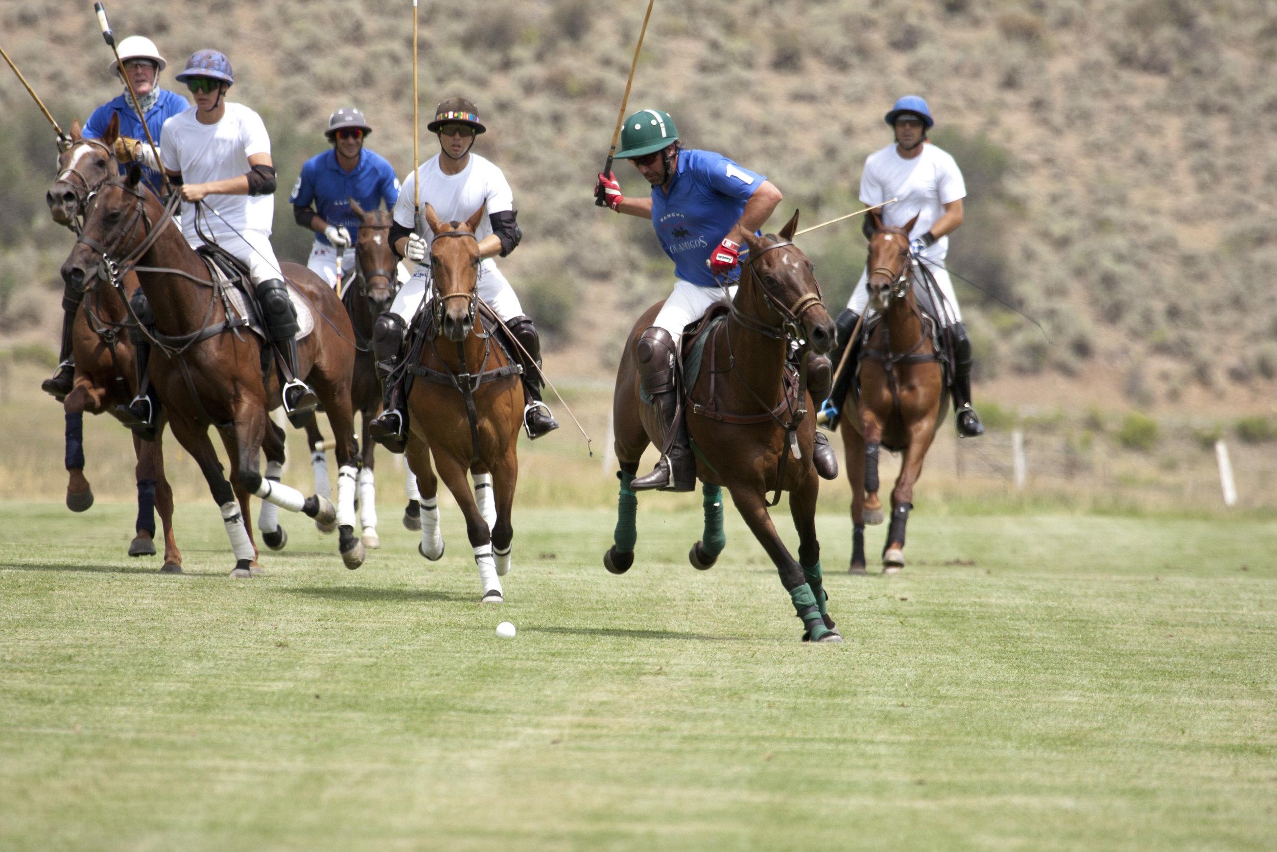 Alex Gooding of Los Amigos Blue is chased by Piocho teammates Hilario Figueras, Carlitos Gracida and Nacho Figueras.