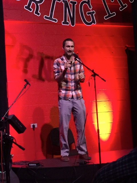 Pablo performs one of his spoken word poems on stage.