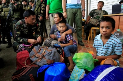 An Army officer talks to residents who were rescued as government troops retake Marawi from the Maute group. Photo by Romeo Ranoco, Reuters.