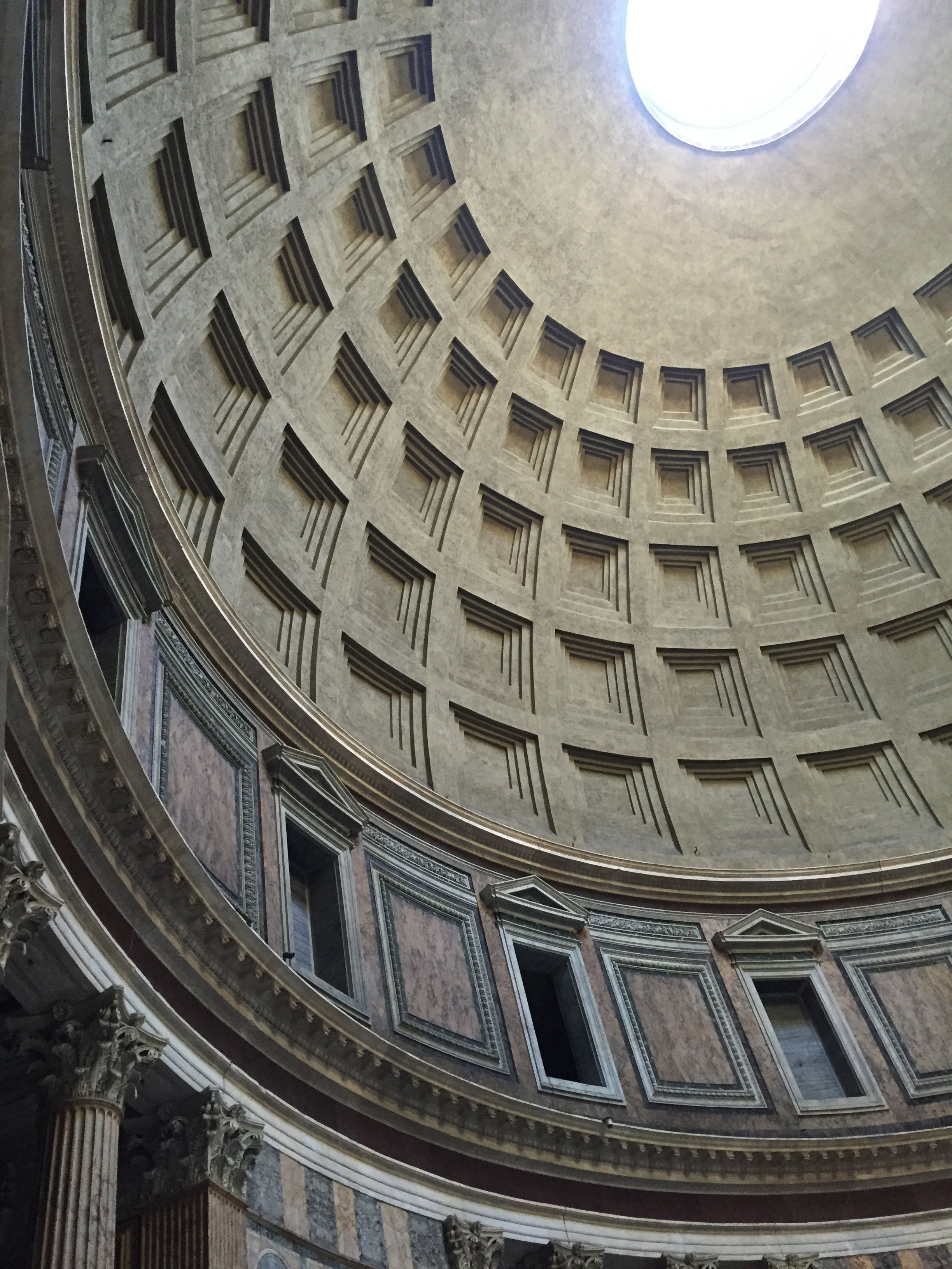 Inside the Pantheon in Rome looking up at the massive dome.