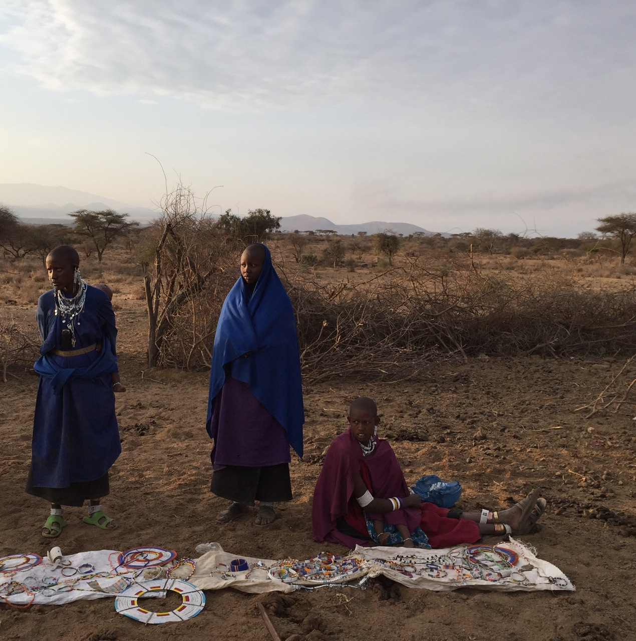 Masai women display their handmade beaded jewelry for sale to our tour group after our visit.
