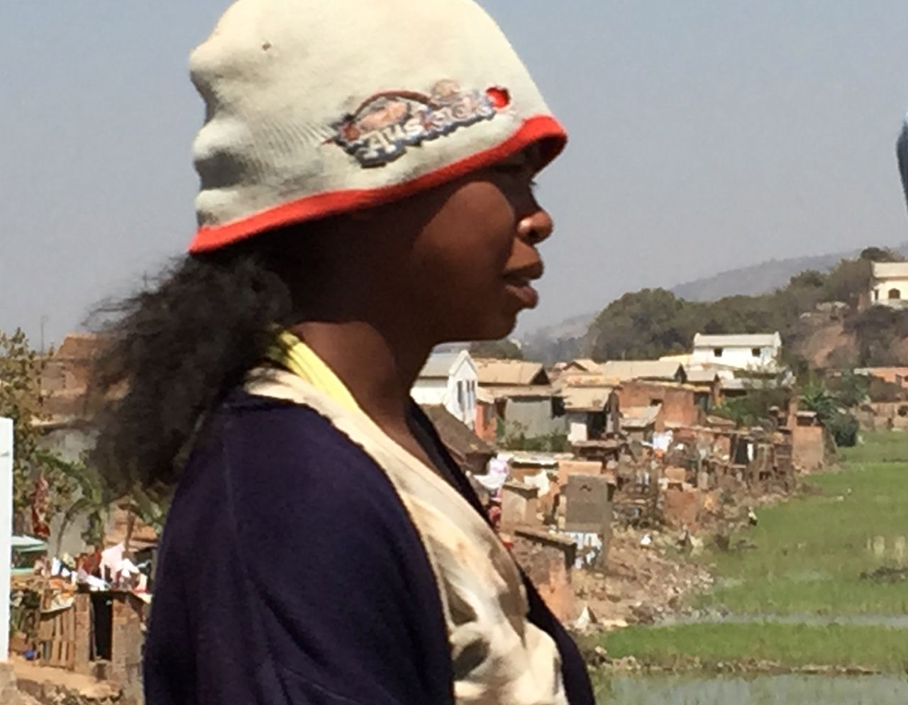 A young Malagasy woman walks along the road from the Antananarivo, the capital city of Madagascar to the airport, through congested traffic and terrible air pollution.