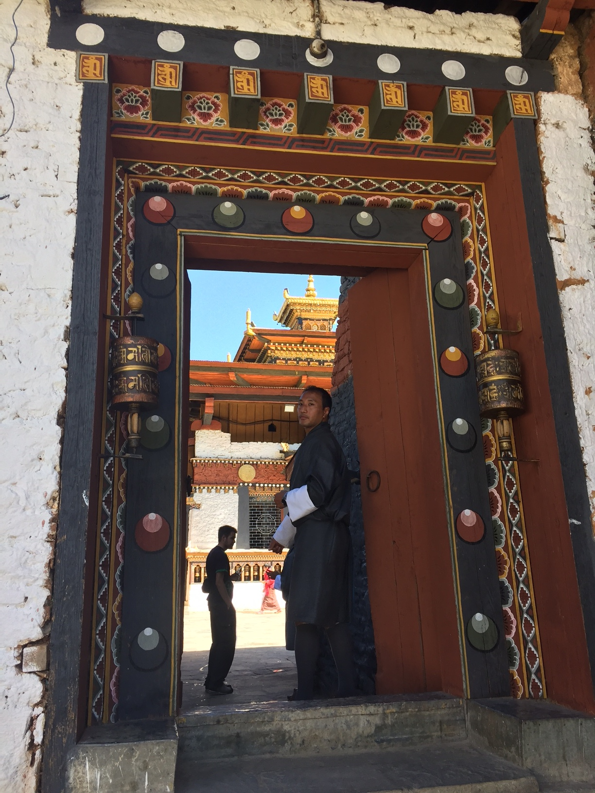 Our tour guide Chen stands at the entrance to a monastery near the city of Thimphu, Bhutan.