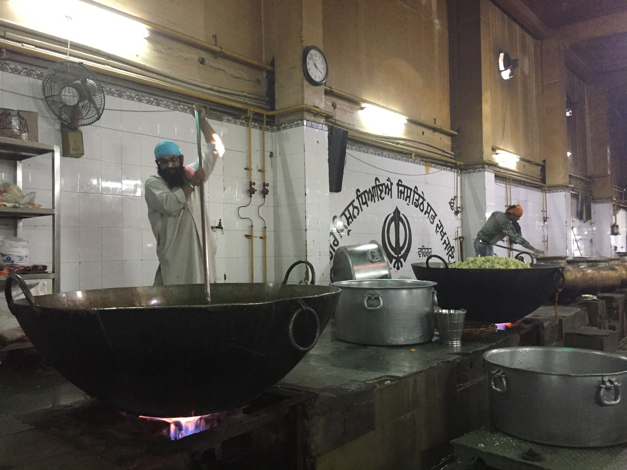 Sikh kitchen staff stir pots of food for the daily meal at Gurudwara Bangla Sahib in Delhi.