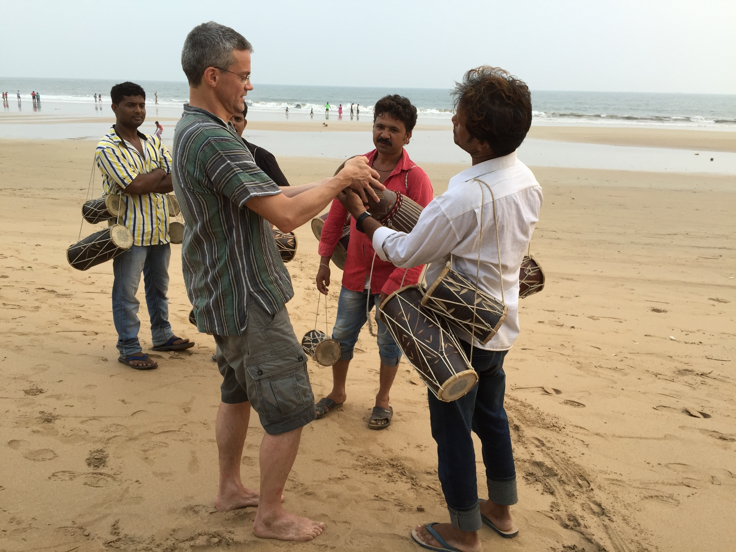 Negotiating with local hawkers to buy a drum at Bogmalo Beach, Goa, India.