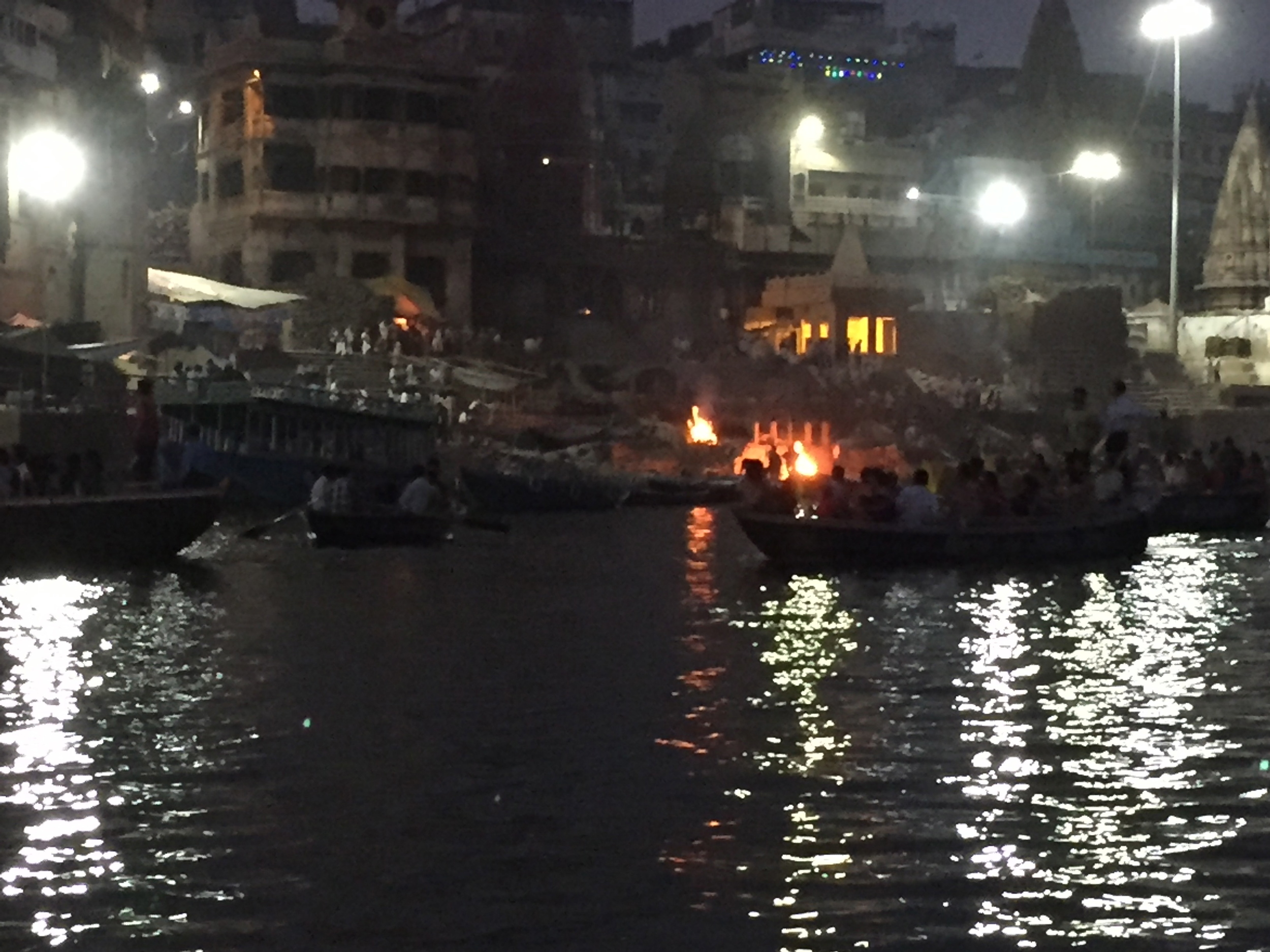 Our boat approaches an ongoing cremation as the sun sets. Bodies are immersed in the waters of the Ganges before cremation. At the same time, pilgrims visiting the river bathe in the waters.