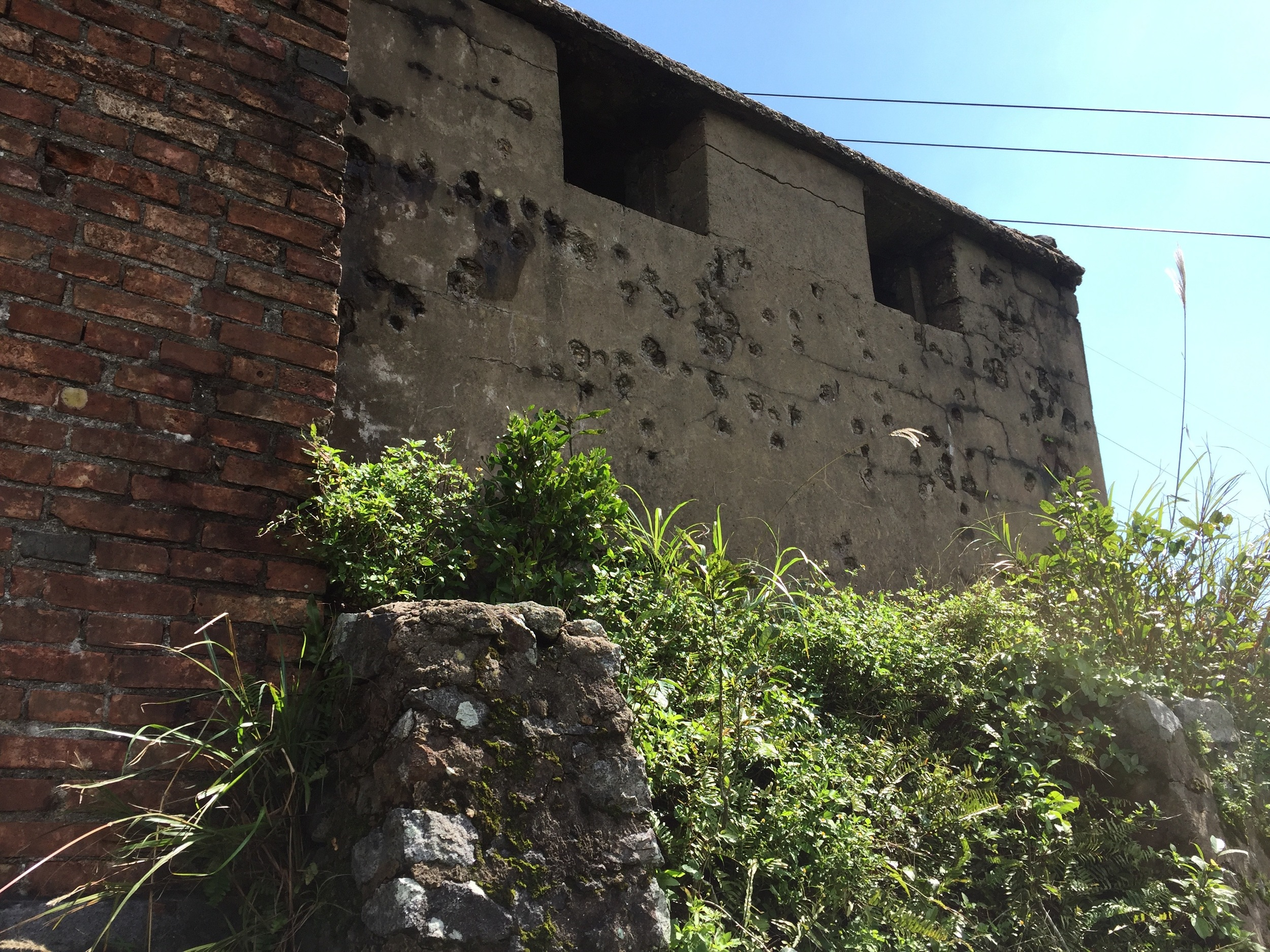 Bullet-hole riddled wall of an old bunker near Danang.