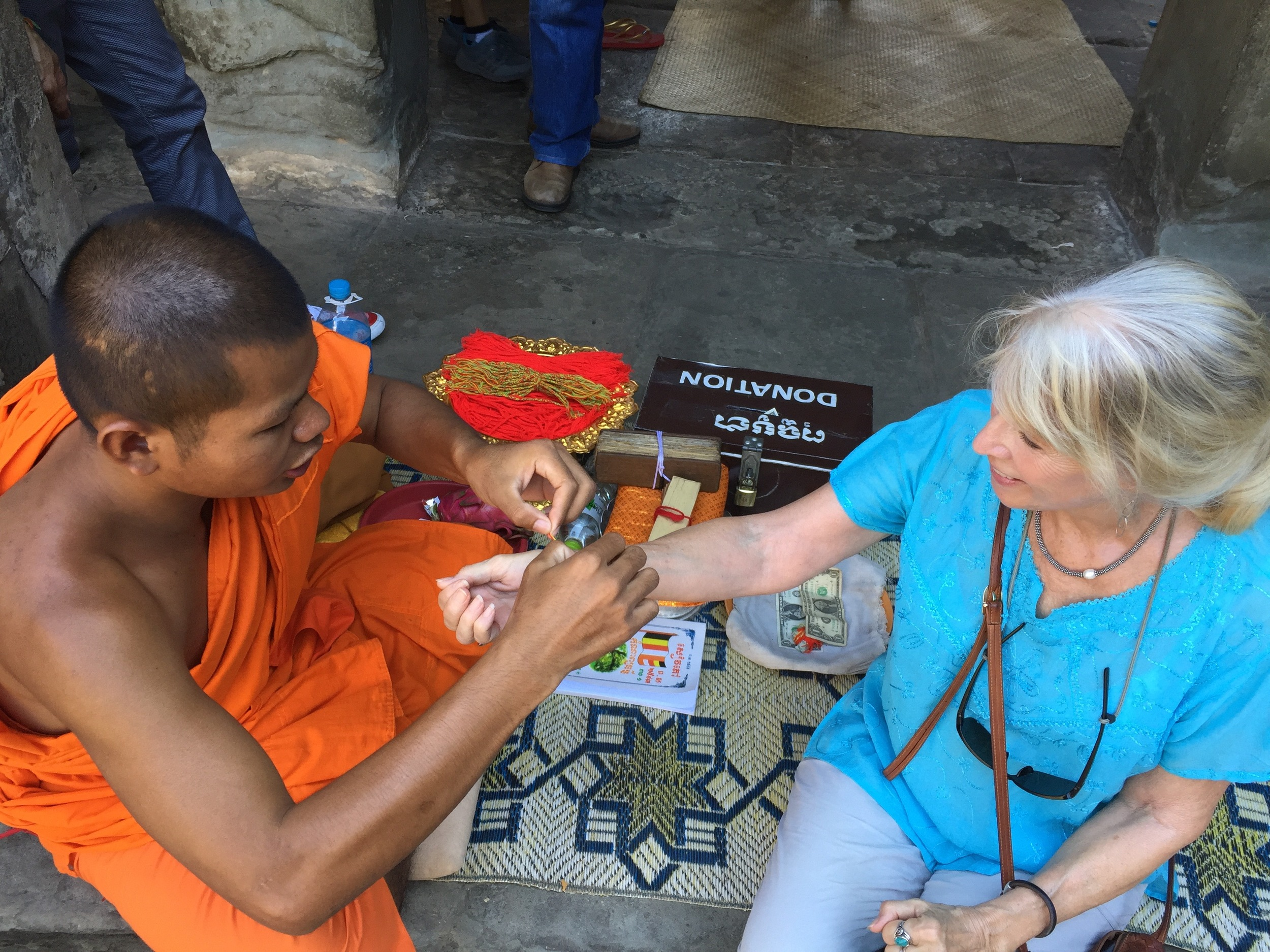Receiving a blessing and a woven bracelet from a Buddhist monk at Angkor Wat, Cambodia.
