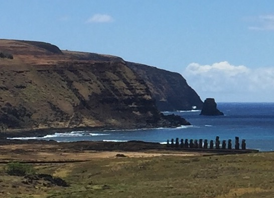 Looking down from the volcanic cliffs of Easter Island to a row of giant Moia along the coast.