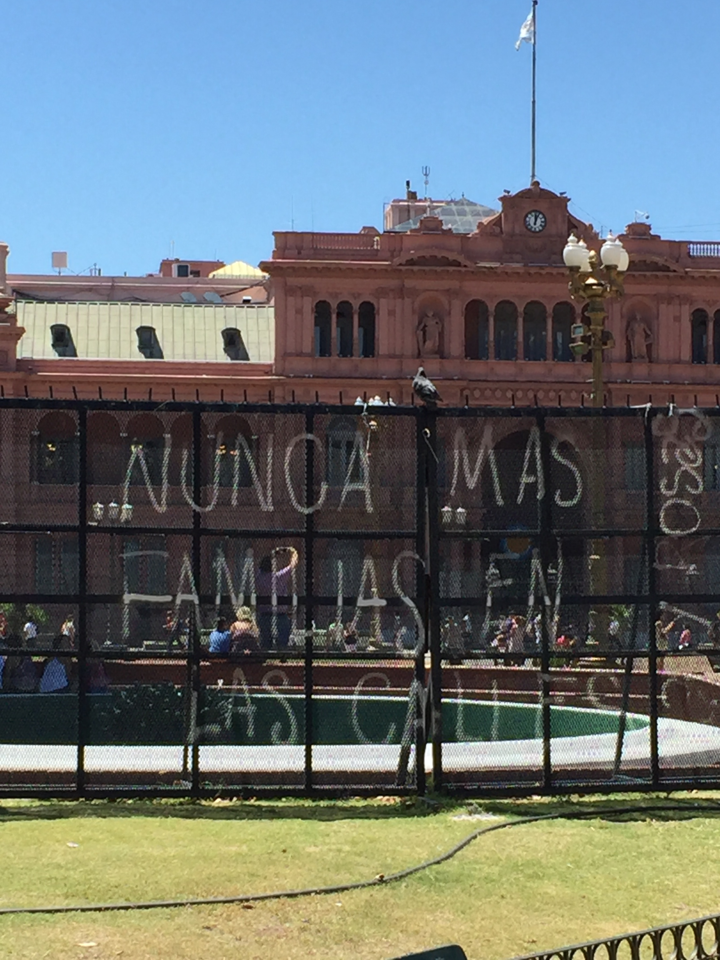 """Someone has painted a message on the chain link fence surrounding the Casa Rosada (Pink House) : """"Nunca mas familias en las calles,"""" meaning """"No more families in the streets,"""" apparently criticizing homelessness in the city."""