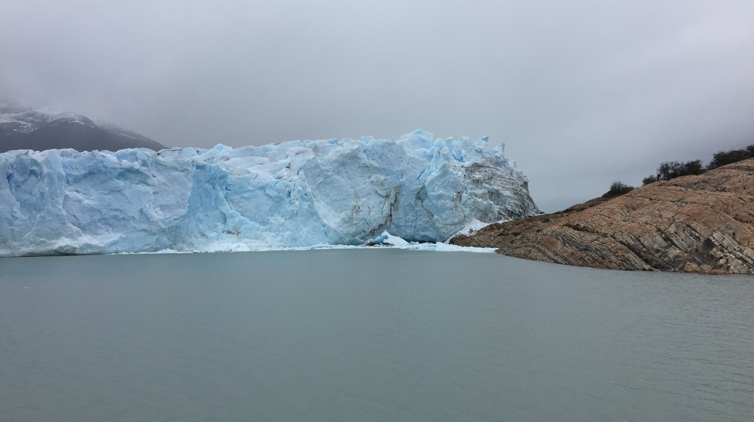 This is where the front of the glacier attaches to a rock face, forming a dam that periodically collapses when the weight of the water overcomes the ice.