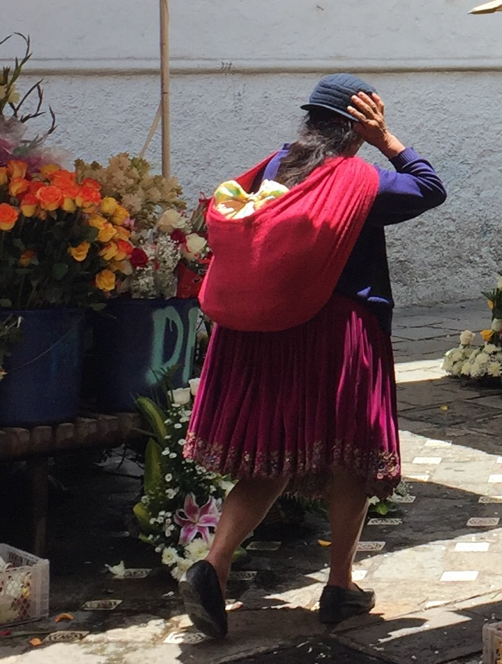 Woman walking through the flower market in Cuenca's downtown.