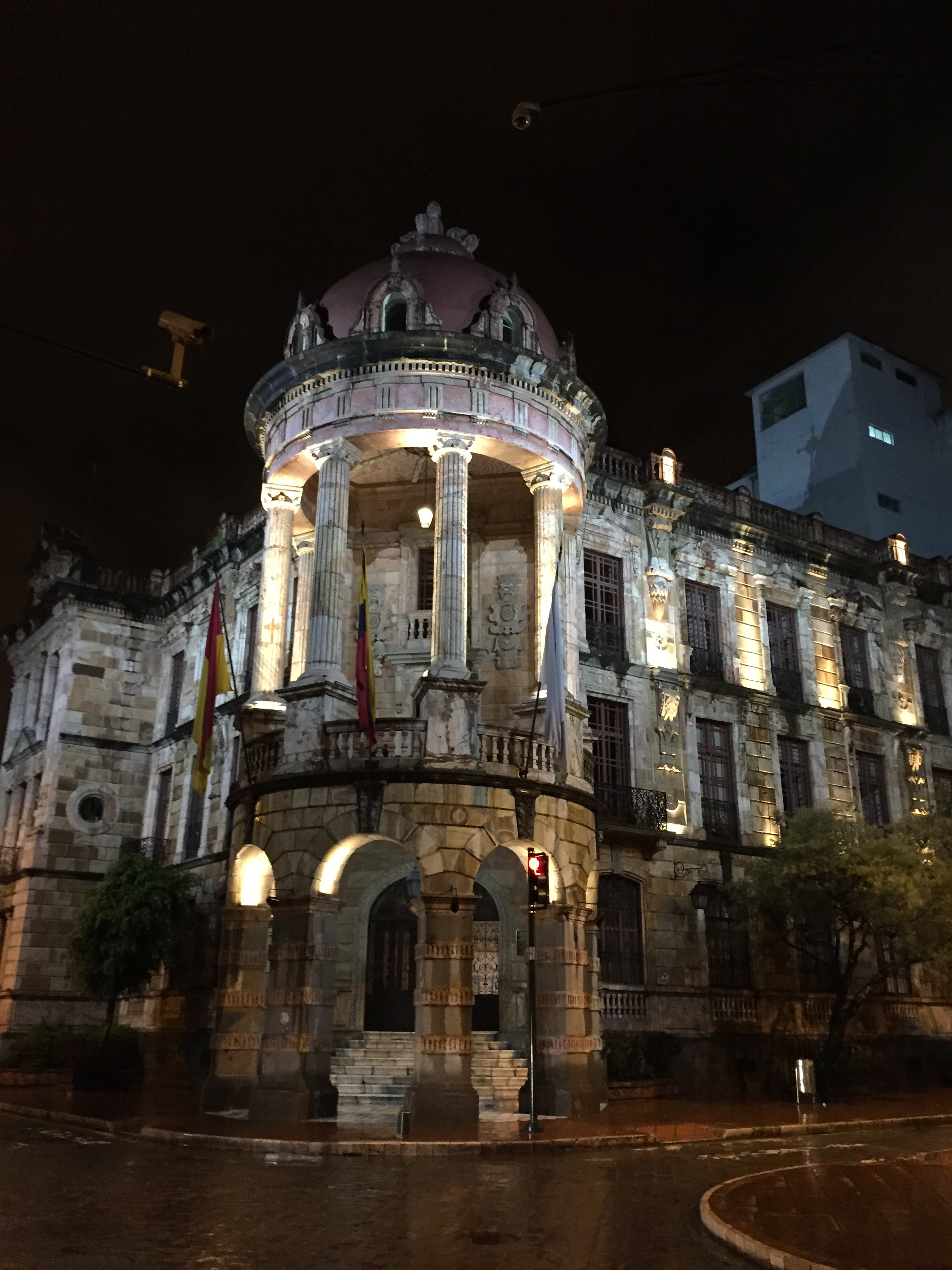 Historic limestone building lit up at night in downtown Cuenca, Ecuador.