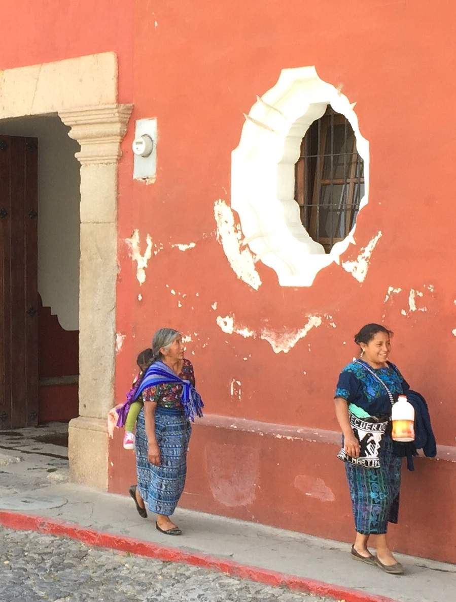 TWo Mayan women walking along a city street in Anitigua...note the cobblestone street.
