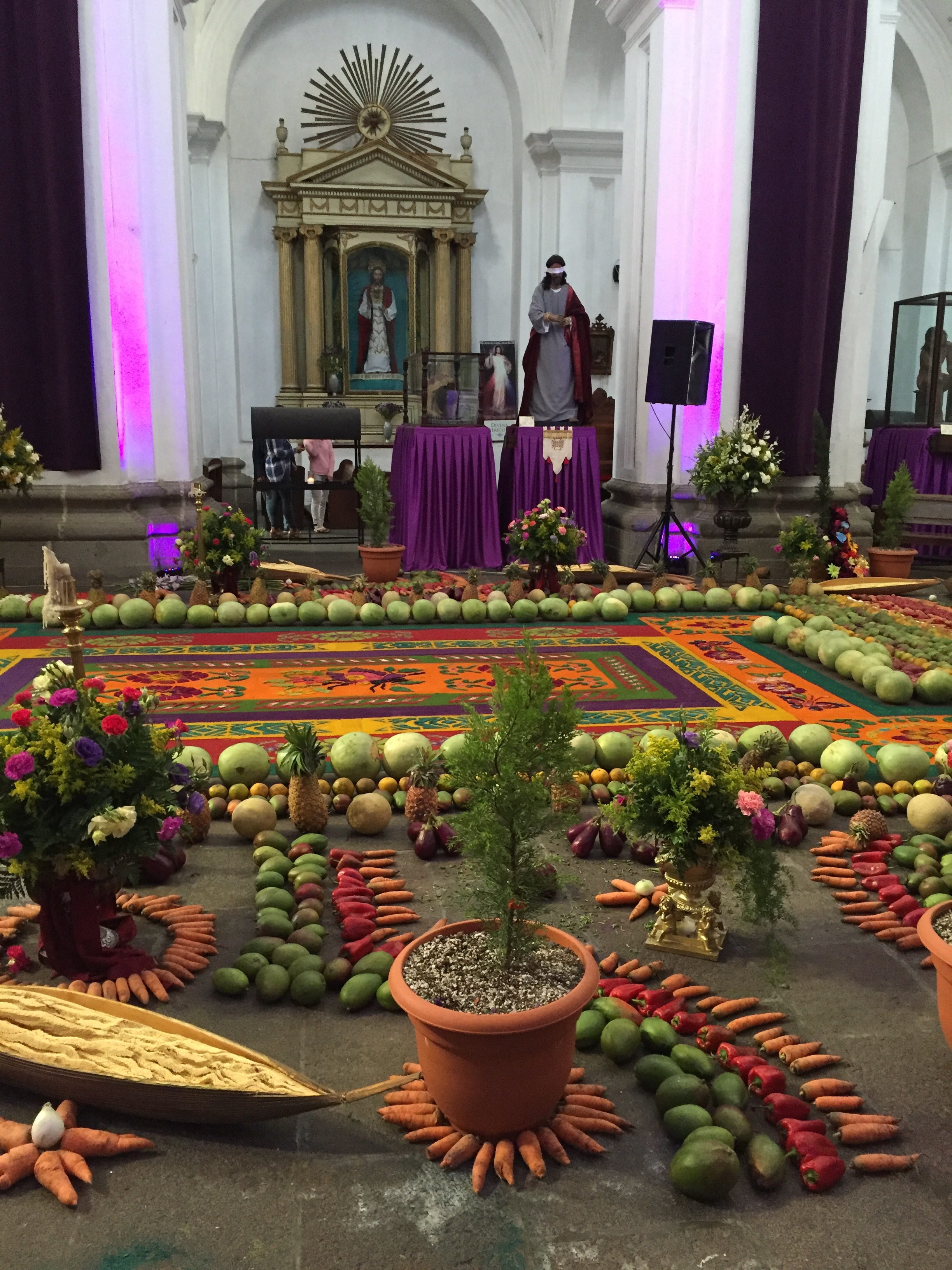 A local church decorated in traditional style for Semana Santa week. Note the sawdust carpet and the cornucopia of fruits and vegetables.