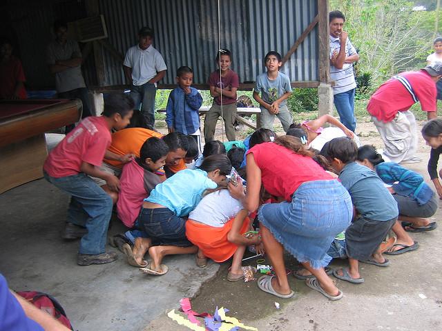 Children in Piedras Negras, Honduras scramble for pinata treats.