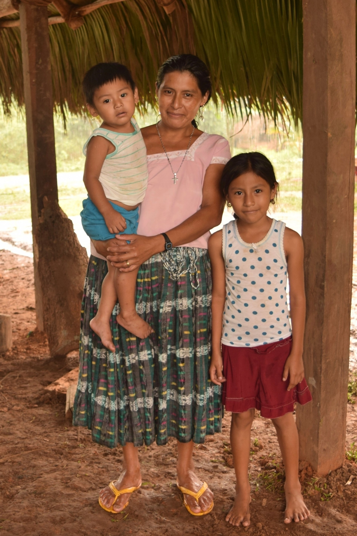 Luciya Coc and her children, Jenny and Namar Acal, stand in their newly built house before the walls are up - Photo by Robin McCarthy