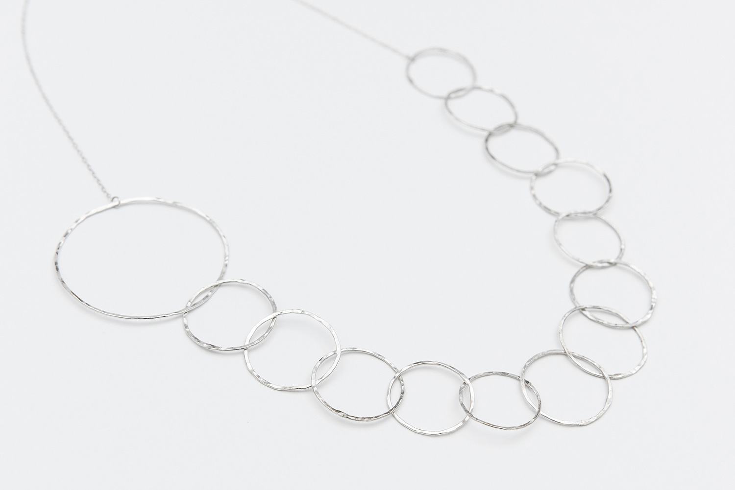 This hammered silver jewelry is handmade by Bev Feldman of Linkouture in Somerville Massachusetts. Linkouture offers luxury matching bracelets, necklaces, and earrings both locally and online. Each piece is elegant, versatile, and has unique character! On-white jewelry product photography and outdoor lifestyle photography for Linkouture is by Lorna Stell Photo, based in Somerville Massachusetts. Lorna Stell is a portrait and wedding photographer for families, bloggers, and entrepreneurs in Boston MA.